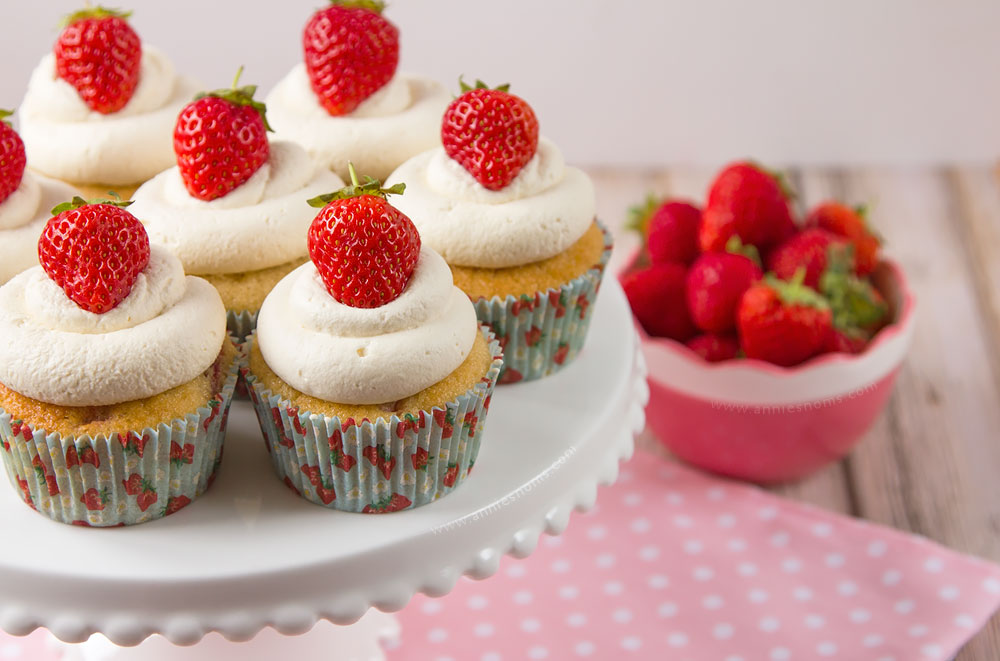 Soft cupcakes filled with chunks of fresh strawberries and topped with sweetened whipped cream and a whole strawberry make these Strawberries and Cream Cupcakes the perfect Summer treat!