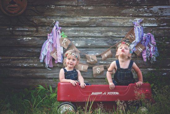 twin girls on a wagon