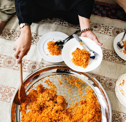 person putting cooked rice on plate