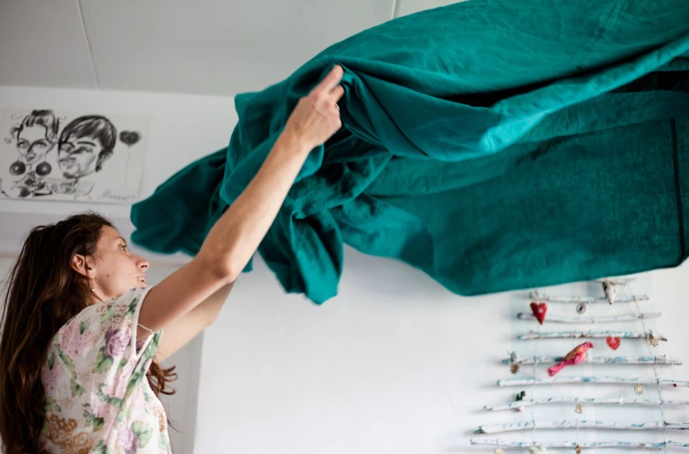 woman preparing to fold a sheet, practicing the touch it once principal for ending clutter