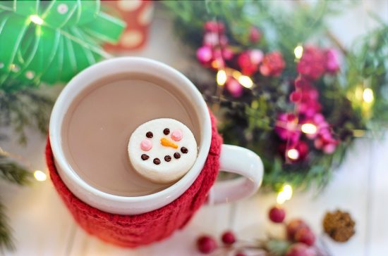 Holiday hot chocolate in a mug that has a drink cozy on it.