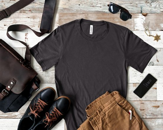 A tshirt, bag, shoes, pants, and phone laid out together on a flat surface.