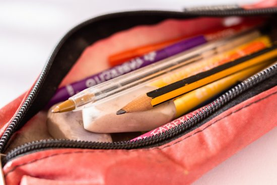 Pens and pencils inside of a zipper pouch.