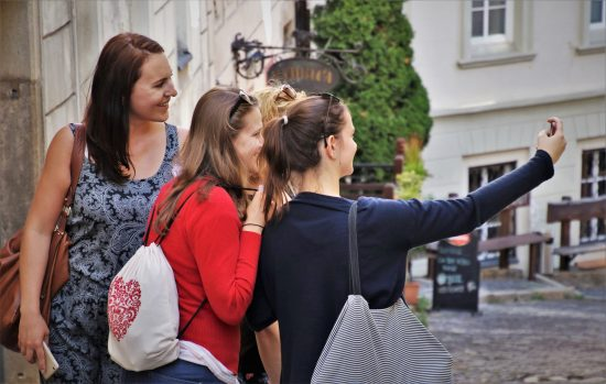 Three women taking a selfie, one with a bag that is on our list of easy sewing projects for beginners.